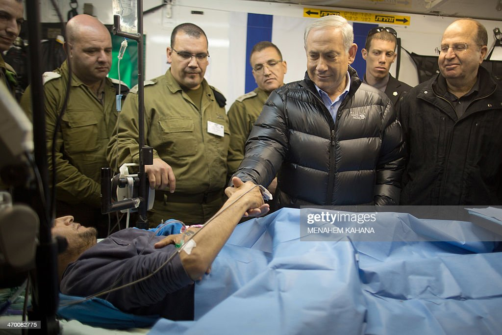 Israeli Prime Minister Benjamin Netanyahu (2R) shakes hands with a Syrian man, who was wounded in the ongoing violence in Syria, as he lies in a military hospital located in the Golan Heights near the border with Syria on February 18, 2014. Since the Syrian conflict erupted almost three years ago hundreds of Syrians have received treatment in Israeli hospitals.