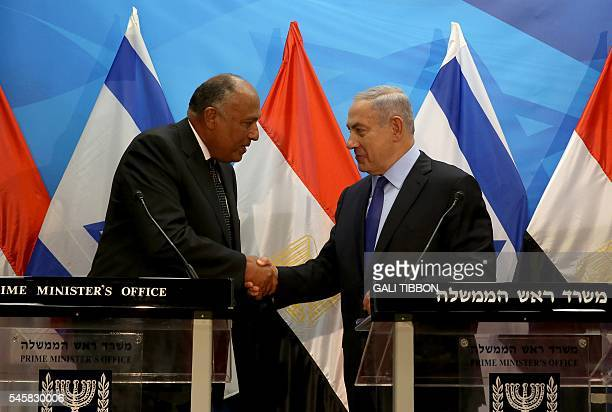 Israeli Prime Minister Benjamin Netanyahu shakes hands with Egyptian Foreign Minister Sameh Shoukry after giving a joint statement prior to their...