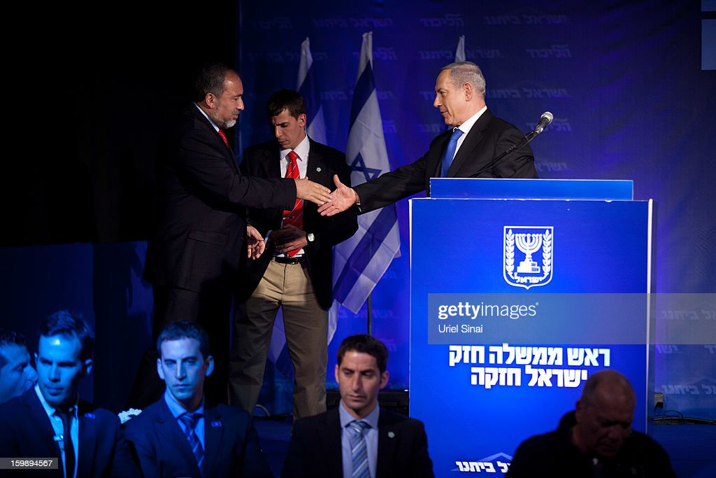 Israeli Prime Minister Benjamin Netanyahu shakes hands with Former Israel Minister for Foreign Affairs Avigdor Liberman at his election campaign headquarters on Janurary 23, 2013 in Tel Aviv, Israel. Exit polls suggested that current Prime Minister Benjamin Netanyahu will return to office, although he performed worse than expected.