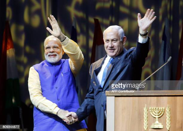 Israeli Prime Minister Benjamin Netanyahu shakes hands with his Indian counterpart Narendra Modi during a meeting with Indian community at the Tel...