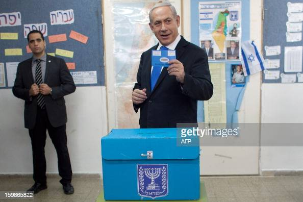 Israeli Prime Minister Benjamin Netanyahu shows his ballot before casting it at a polling station in Jerusalem on January 22 as Israel residents...