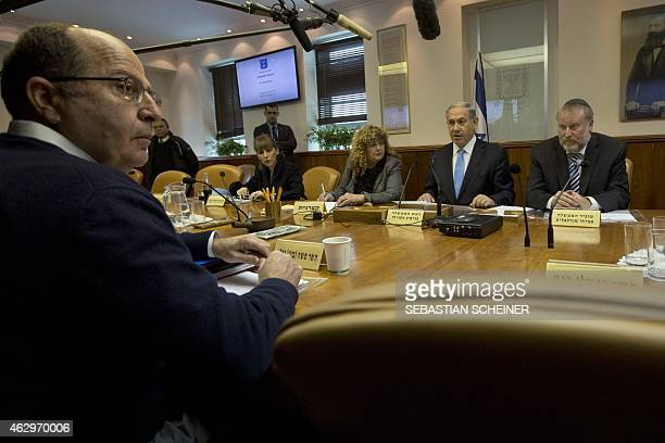 Israeli Prime Minister Benjamin Netanyahu sits in front of Defence Minister Moshe Yaalon as he chairs the weekly cabinet meeting at his Jerusalem...