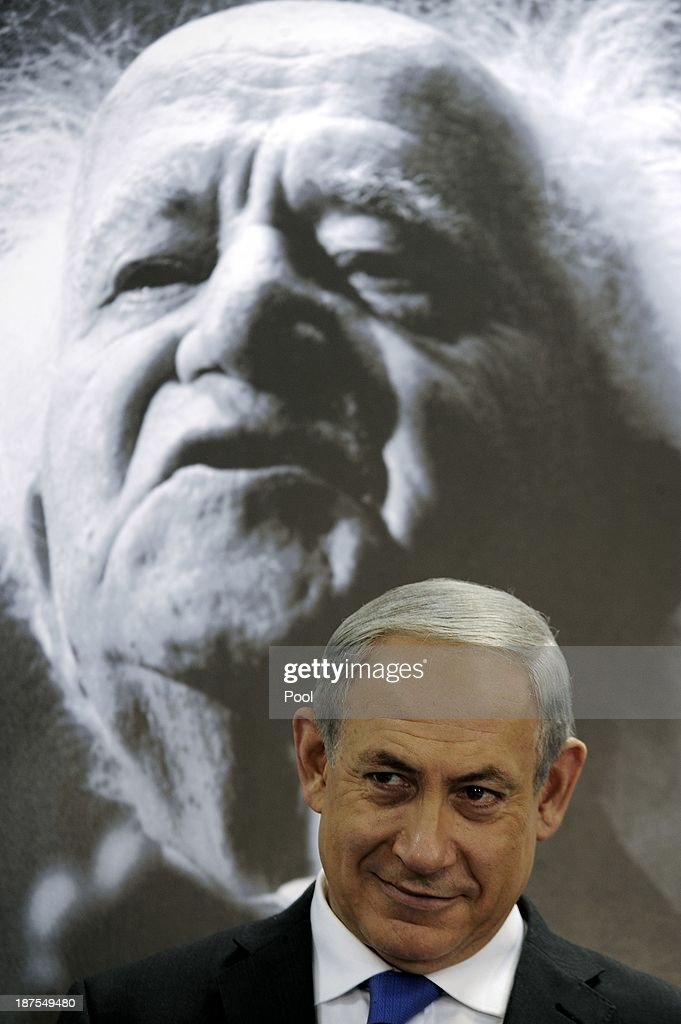 Israeli Prime Minister Benjamin Netanyahu sits under a portrait of the first Israeli prime minister David Ben Gurion as he speaks during a cabinet...