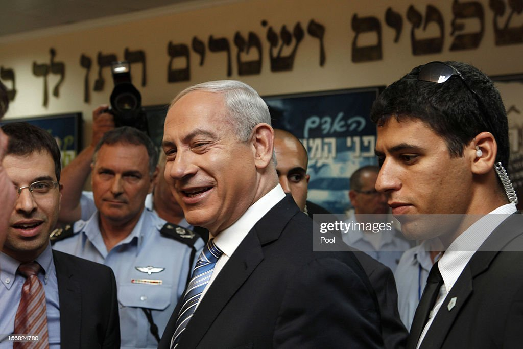 Israeli Prime Minister Benjamin Netanyahu (C) smiles during his visit to the national police headquarters on November 22, 2012 in Jerusalem, Israel. A ceasefire took hold on November 21 in and around Gaza after a week of cross-border violence between Israel and Palestinian militants, although a police spokesman reported that twelve rockets fired from the Gaza Strip hit Israel in the hours that followed the agreement.