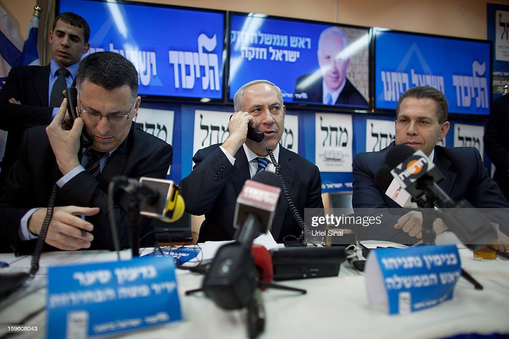 Israeli Prime Minister Benjamin Netanyahu (2nd R) speaks on the phone with potential voters ahead of the upcoming Israeli elections on January 17, 2013. in Tel Aviv, Israel. Israeli elections are scheduled for January 22 and so far showing a majority for the Israeli right.