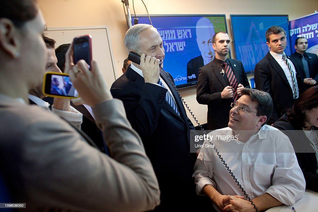 Israeli Prime Minister Benjamin Netanyahu (3rd L) speaks on the phone with potential voters ahead of the upcoming Israeli elections on January 17, 2013. in Tel Aviv, Israel. Israeli elections are scheduled for January 22 and so far showing a majority for the Israeli right.