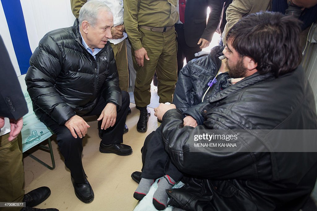 Israeli Prime Minister Benjamin Netanyahu (L) speaks to a Syrian man holding his child, who was wounded in the ongoing violence in Syria, as he visits a military hospital located in the Golan Heights near the border with Syria on February 18, 2014. Since the Syrian conflict erupted almost three years ago hundreds of Syrians have received treatment in Israeli hospitals.