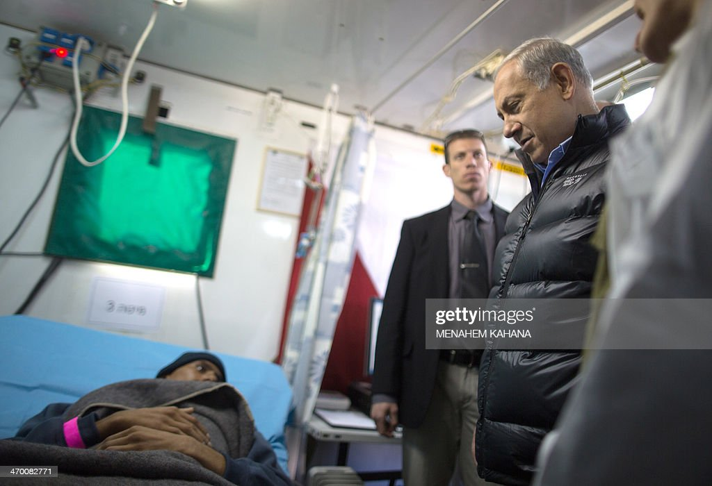 Israeli Prime Minister Benjamin Netanyahu (R) speaks with a Syrian man, who was wounded in the ongoing violence in Syria, as he visits a military hospital located in the Golan Heights near the border with Syria on February 18, 2014. Since the Syrian conflict erupted almost three years ago hundreds of Syrians have received treatment in Israeli hospitals.
