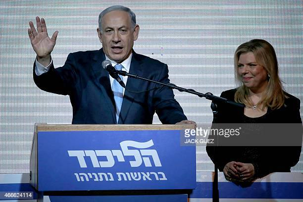 Israeli Prime Minister Benjamin Netanyahu stands on stage with his wife Sara as he reacts to exit poll figures in Israel's parliamentary elections...
