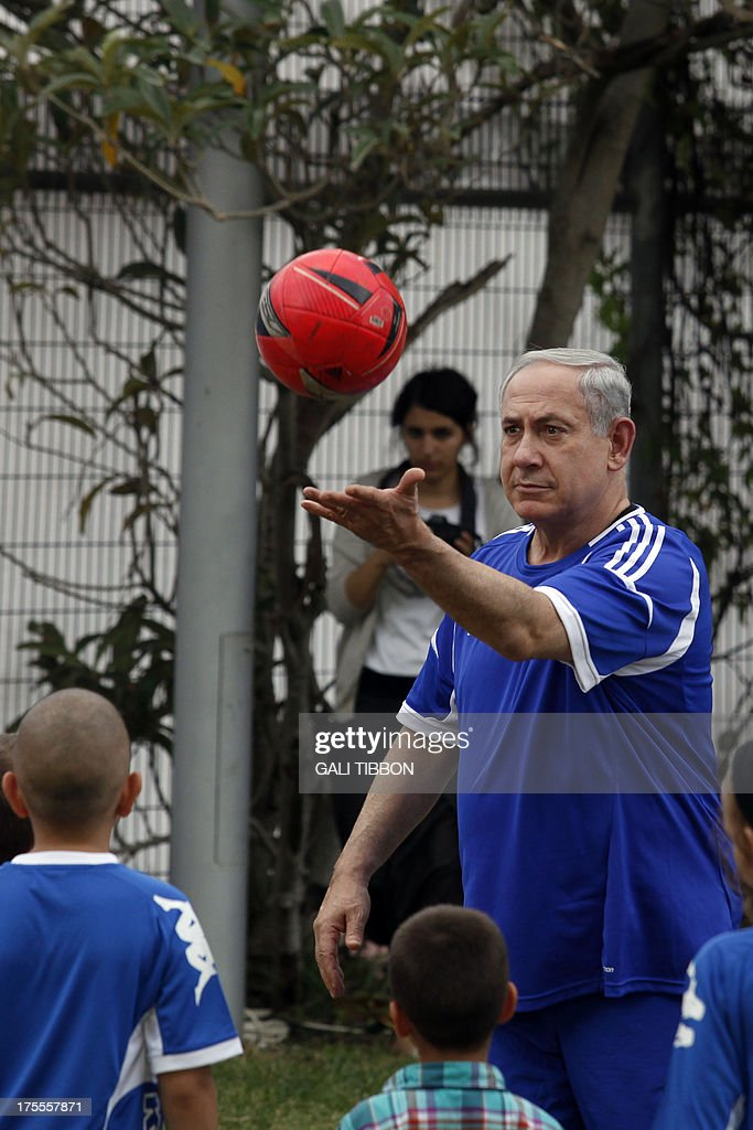Israeli Prime Minister Benjamin Netanyahu takes part in a football event with young Israeli cancer patients, attended by FC Barcelona players, near Tel Aviv on August 4, 2013.