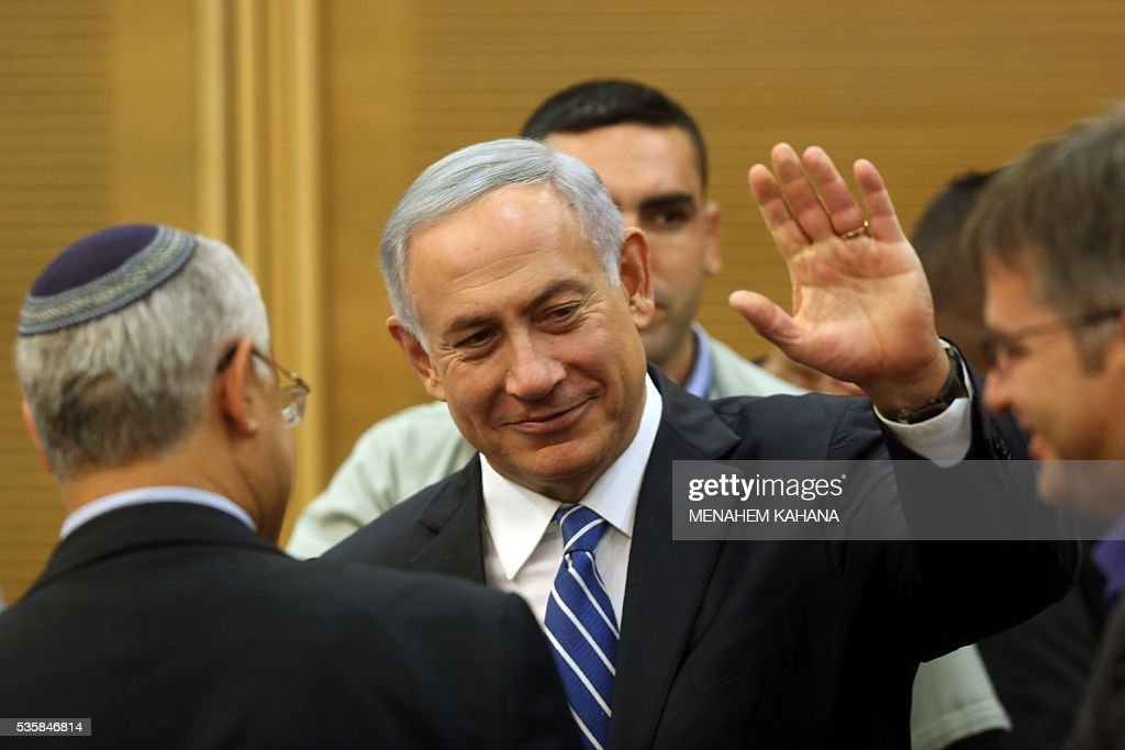 Israeli Prime Minister Benjamin Netanyahu waves as he arrives for a meeting of his Likud party at the Knesset (parliament) in Jerusalem on May 30, 2016. Netanyahu's cabinet approved the entry of ultra-nationalist Avigdor Lieberman to the ruling coalition as defence minister, after defusing opposition from another partner, the government said. / AFP / MENAHEM