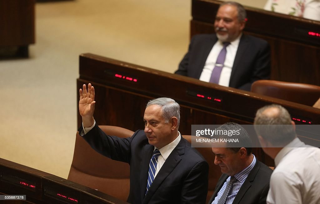 Israeli Prime Minister Benjamin Netanyahu waves during a parliament session in which MPs approved Israeli ultra-nationalist Avigdor Lieberman (top) as new defence minister, on May 30, 2016 in Jerusalem. The Israeli parliament approved Lieberman as the country's new defence minister hours after the cabinet endorsed him. Lieberman, who has pledged harsh measures against Palestinian 'terrorists', was approved by 55 members of the 120-seat Knesset while 43 voted against, one abstained and the others were absent. KAHANA