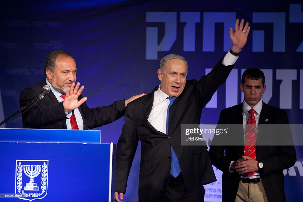 Israeli Prime Minister Benjamin Netanyahu waves to his supporters as he arrives with Former Israel Minister for Foreign Affairs Avigdor Liberman at his election campaign headquarters on Janurary 23, 2013 in Tel Aviv, Israel. Exit polls suggested that current Prime Minister Benjamin Netanyahu will return to office, although he performed worse than expected.