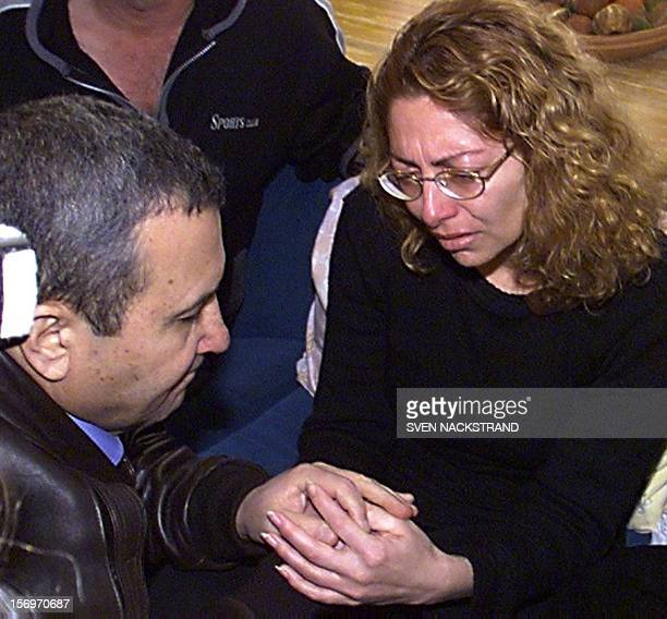 Israeli Prime Minister Ehud Barak comforts Shosh Malcha in Metulla 01 February 2000 as he pays a condolences visit to the family of Israeli soldier...