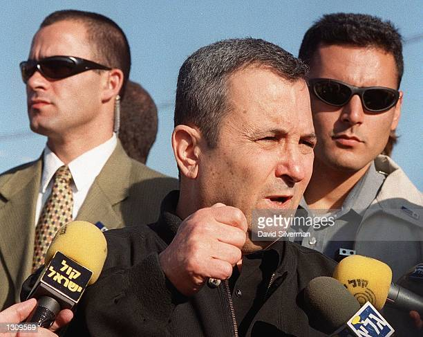 Israeli Prime Minister Ehud Barak flanked by secret service bodyguards addresses reporters during a visit to a major army base December 5 2000 on the...
