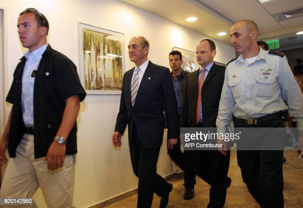 Israeli Prime Minister Ehud Olmert accompanied by an unidentified Israeli military officer and security guards walks through the halls of the Prime...