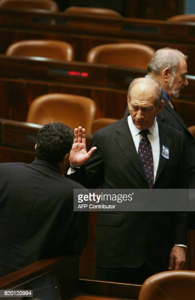 Israeli Prime Minister Ehud Olmert exchanges words with his Defense Minister Amir Peretz on the floor of the Knesset at the conclusion of a memorial...
