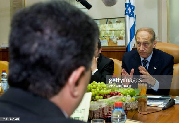 Israeli Prime Minister Ehud Olmert gestures as he speaks towards his Defense Minister Amir Peretz during the weekly cabinet meeting in his Jerusalem...