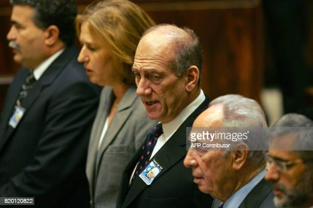 Israeli Prime Minister Ehud Olmert is flanked by his cabinet ministers Amir Peretz Tzipi Livni Shimon Peres and Eli Yishai as they sing Hatikva the...