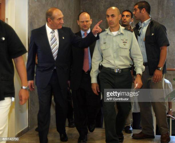Israeli Prime Minister Ehud Olmert points to an aid as he walks accompanied by an unidentified Israeli military officer and security guards through...