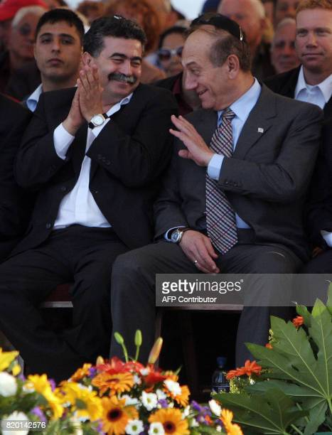 Israeli Prime Minister Ehud Olmert shares a light moment with his Defense Minister Amir Peretz as they attend a ceremony in Jerusalem late afternoon...