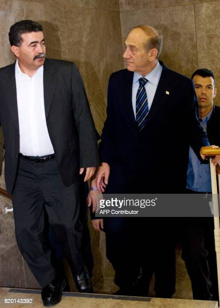 Israeli Prime Minister Ehud Olmert speaks with his Defense Minister Amir Peretz as they arrive in Olmert's Jerusalem offices to attend to weekly...