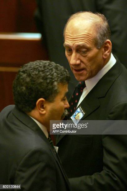 Israeli Prime Minister Ehud Olmert talks with his Defense Minister Amir Peretz during a memorial marking eleven years since Prime Minister Yitzhak...
