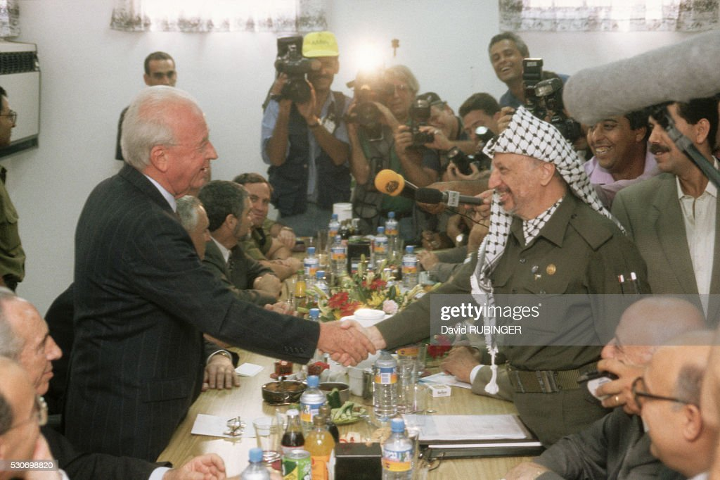 Israeli Prime Minister <a gi-track='captionPersonalityLinkClicked' href=/galleries/search?phrase=Yitzhak+Rabin&family=editorial&specificpeople=94269 ng-click='$event.stopPropagation()'>Yitzhak Rabin</a> shakes Palestinian Authority President <a gi-track='captionPersonalityLinkClicked' href=/galleries/search?phrase=Yasser+Arafat+-+Politiek+leider&family=editorial&specificpeople=118625 ng-click='$event.stopPropagation()'>Yasser Arafat</a>'s hand at the Erez Checkpoint, on the border of the Gaza Strip. Israeli foreign minister Shimon Peres can be seen at lower left.