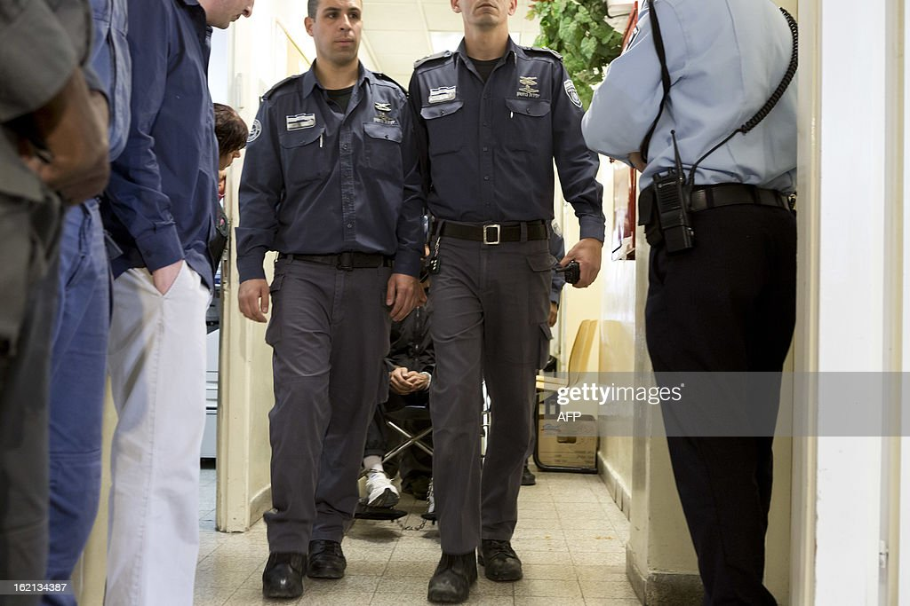 Israeli prison service police surround Palestinian hunger strike prisoner Samer Issawi (C) while being wheeled in his wheel chair out from a hearing in the Magistrate's Court in Jerusalem, on February 19, 2013. Hundreds of Palestinians are on a one-day hunger strike in solidarity with Issawi who has been fasting for the past 209 days.