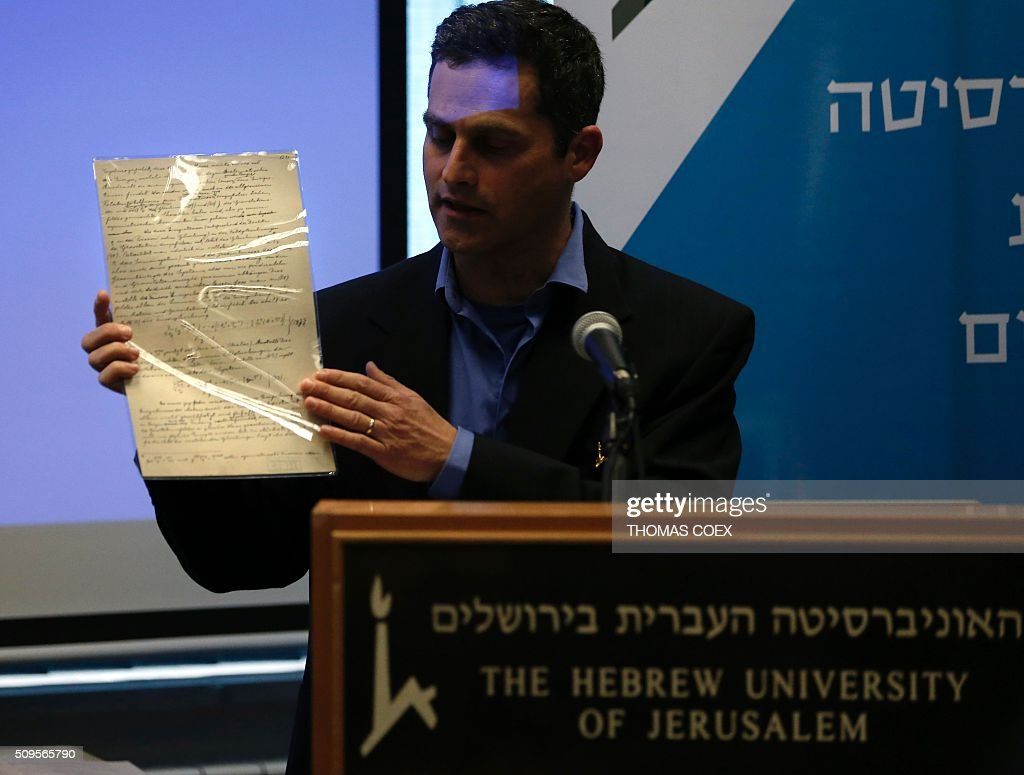 Israeli Professor Barak Kol, head of the physics department at the Hebrew University of Jerusalem on February 11, 2016 shows the original document written by Albert Einstein related to his prediction of the existence of gravitational waves. The Einstein theory was developed by Einstein 100 years ago, but had never been proved. One document is the first in which Einstein ever presented his theory of gravitational waves, the other is a page from the 46-page Theory of Relativity. / AFP / THOMAS COEX