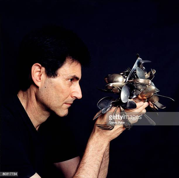 Israeli psychic Uri Geller with a selection of cutlery he claims to have bent using the power of his mind London 2002