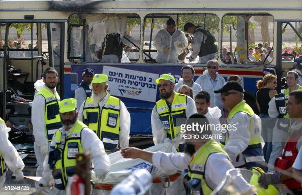Israeli rescue teams evacuate a body from the scene of a twin suicide bombing of two buses in the southern Israeli town of Beersheva 31 August 2004...