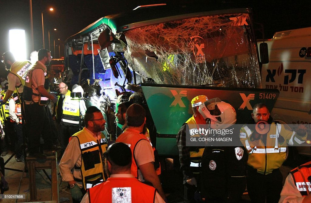 Israeli rescue workers are seen at scene of a bus-truck collision in the main road linking Jerusalem to Tel Aviv on February 14, 2016 which killed at least six people and wounded more than 20. / AFP / GIL COHEN-MAGEN