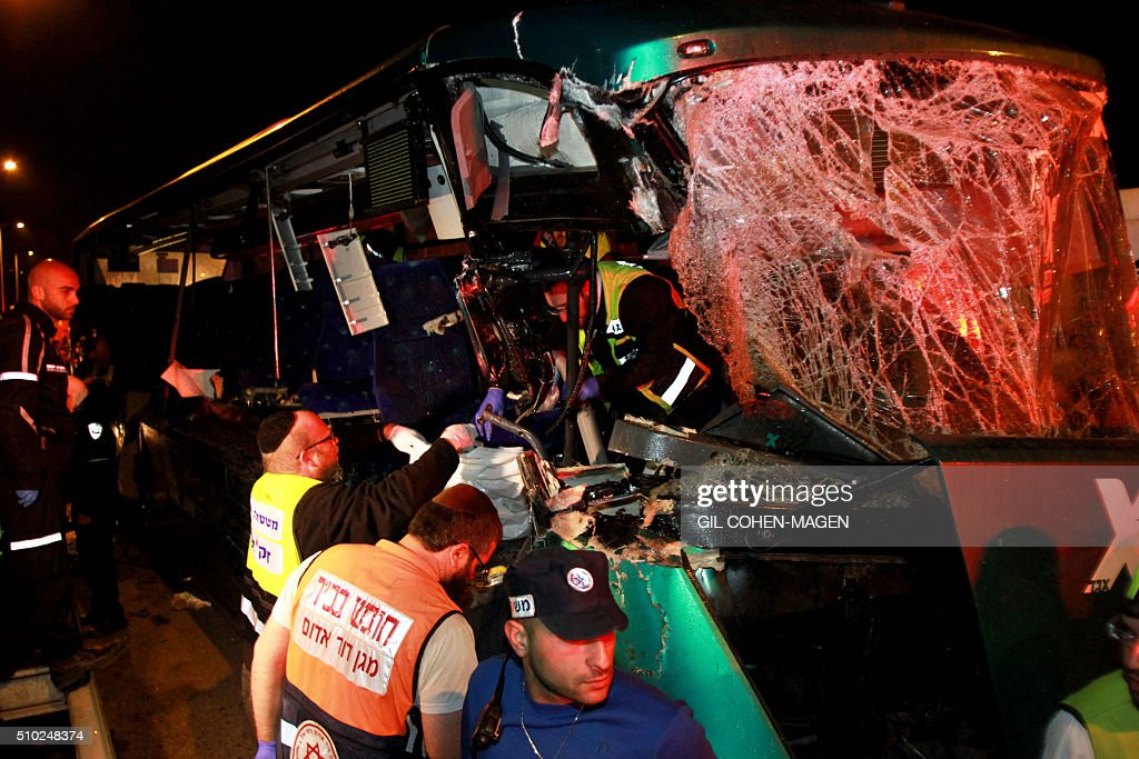 Israeli rescue workers are seen at the scene of a bus-truck collision in the main road linking Jerusalem to Tel Aviv on February 14, 2016 which killed at least six people and wounded more than 20. / AFP / GIL COHEN-MAGEN