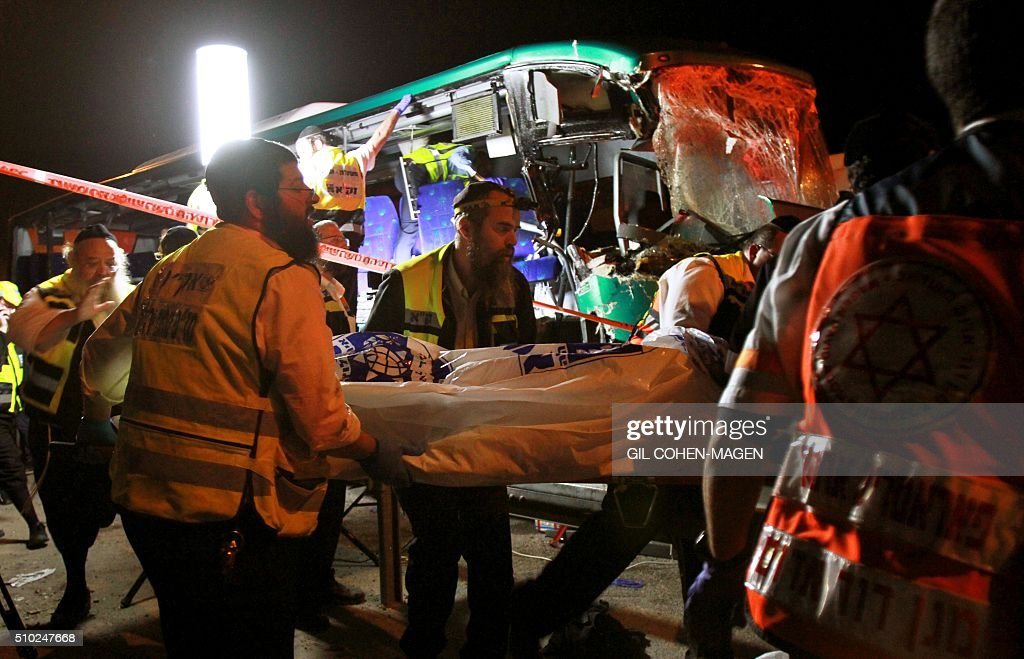 Israeli rescue workers evacuate a body at cene of a bus-truck collision in the main road linking Jerusalem to Tel Aviv on February 14, 2016 which killed at least six people and wounded more than 20. / AFP / GIL COHEN-MAGEN