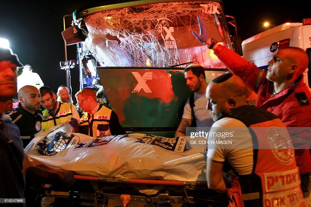 Israeli rescue workers evacuate a body at the scene of a bus-truck collision in the main road linking Jerusalem to Tel Aviv on February 14, 2016 which killed at least six people and wounded more than 20. / AFP / GIL COHEN-MAGEN