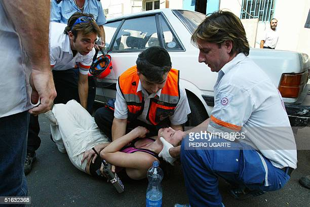 Israeli rescue workers help a woman who had en epileptic attack after a suicide bombing in Tel Aviv 01 November 2004 At least four people were killed...