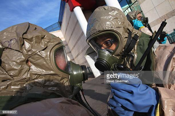 Israeli rescue workers wear DuPont protective suits as they deploy outside a shopping mall during a training exercise simulating a chemical warfare...