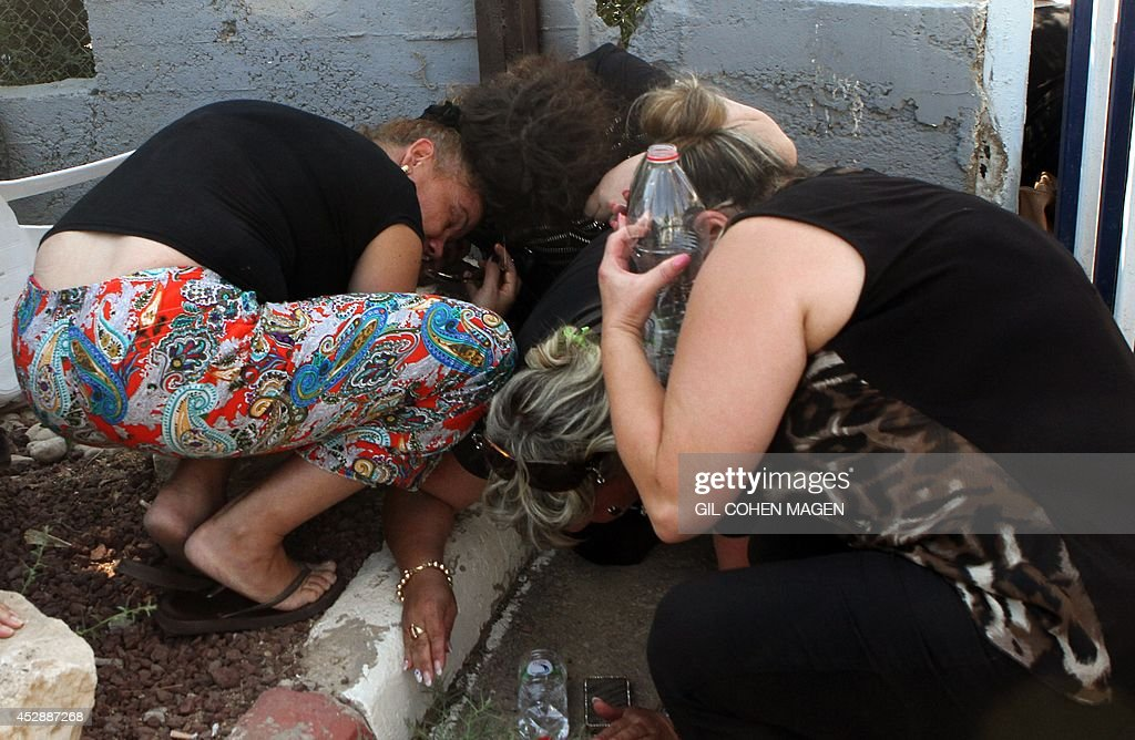 Israeli residents and relatives take cover from a rocket attack from Palestinian militants from the Gaza Strip during the funeral of Israeli soldier...