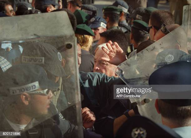Israeli rightwing opposition leader Ariel Sharon is flanked by security guards as he leaves the AlAqsa mosque compound in Jerusalem's Old City 28...