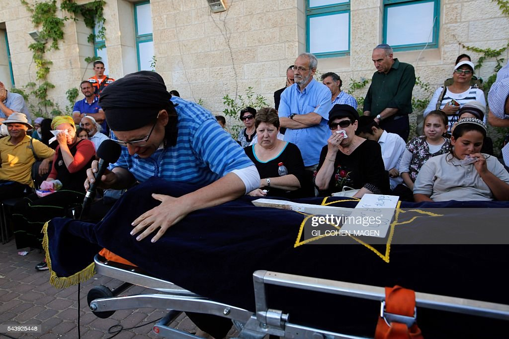 Israeli Rina Yaffa Ariel, mourns over the body of her daughter Hallel, a 13-year-old girl who was fatally stabbed by a Palestinian attacker in her home, during her funeral in the Kiryat Arba settlement outside the Israeli occupied city of Hebron on June 30, 2016. The Israeli army said that a young Palestinian killed Hallel in her bed after breaking into her home in the Kiryat Arba settlement outside the flashpoint city of Hebron. Security personnel rushed to the house and fired on the attacker, who wounded a guard before being shot dead, the army said. The girl was taken to hospital in Jerusalem in critical condition and died of her wounds. / AFP / GIL