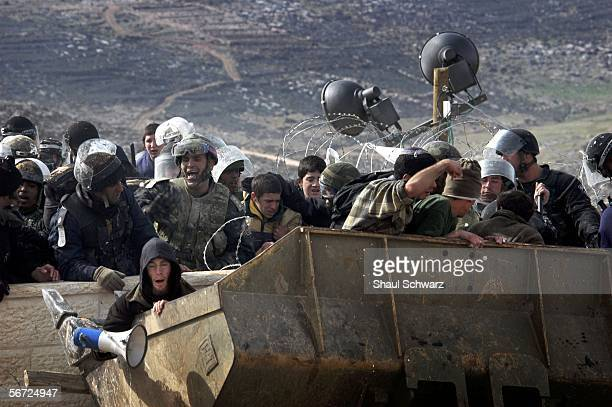 Israeli riot police clash with Israeli settlers as they evacuate them off a roof top using bulldozers on February 1 2006 in the West Bank outpost of...
