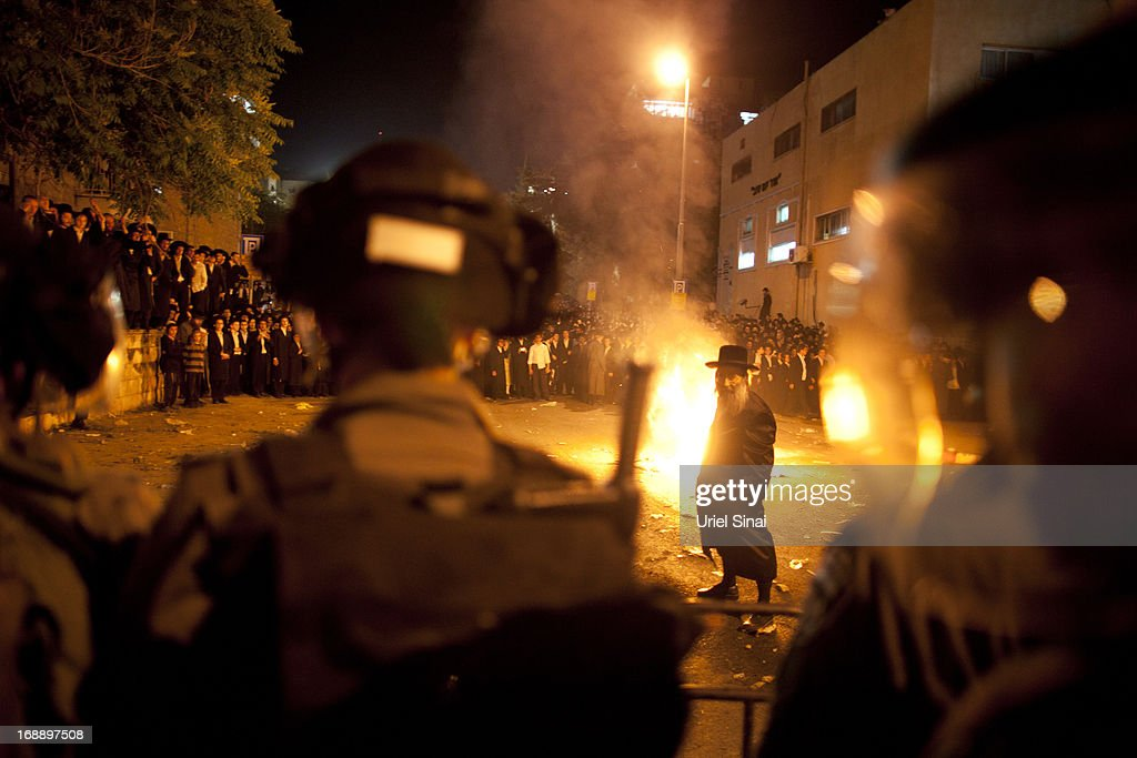 Israeli riot police stand guard as ultra-Orthodox demonstrators set trash bins on fire on May 16, 2013 in Jerusalem, Israel. Tens of Thousands of ultra-Orthodox Israelis have clashed with police after gathering to protest against newly proposed government legislation that would see them drafted into the military.