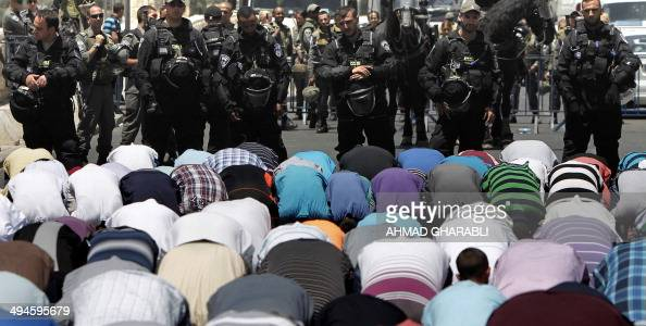 Israeli riot police stand guard behind Palestinian Muslim worshipers attending the Friday prayer outside the Old City of Jerusalem on May 30 2014 AFP...