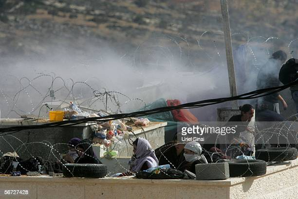 Israeli riot police use water canons on settlers who had barricaded themselves on a roof top February 1 2006 in the West Bank outpost of Amona The...
