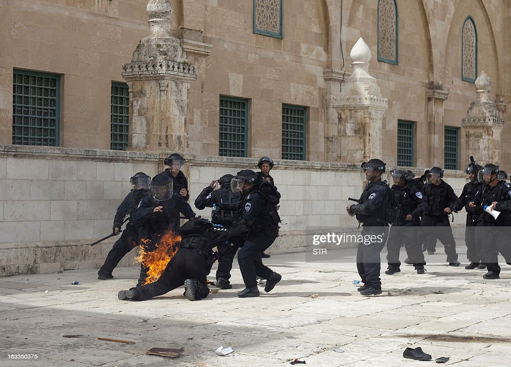 Israeli riot policemen help a comrade after a fire bomb was thrown at him during clashes with Palestinian demonstrators at Jerusalem's al-Aqsa mosque compound following Friday prayers on March 8, 2013. Palestinians enraged by reports that an Israeli policeman mishandled a Koran battled riot officers at Jerusalem's Al-Aqsa mosque compound with stones and petrol bombs, police and witnesses said.
