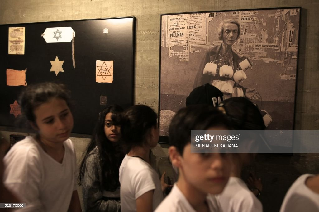 Israeli school children visit the 'From Holocaust to Revival' Museum in Kibbutz Yad Mordechai in southern Israel on May 4, 2016 on the eve of the Holocaust Remembrance Day. The picture on the wall, taken during the World War II period, shows a woman selling armbands bearing the Jewish yellow-star. Holocaust Remembrance Day, commemorating the six million Jews killed by the Nazis during World War II, is an internationally recognized date corresponding to the 27th day of Nisan on the Hebrew calendar and begins this year in the evening of May 4 and ends in the evening of May 5. KAHANA