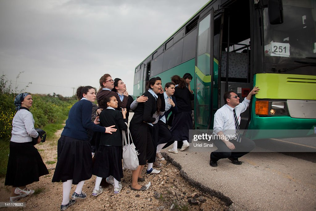 Israeli school girls take cover next to a bus during a rocket attack from the nearby Gaza Strip, on March 12, 2012 in Ashdod, Israel. The UN and EU have appealed for calm as cross border rocket strikes continued into a fourth day between the Gaza Strip and Israel, which have so far resulted in 23 Palestinian deaths.