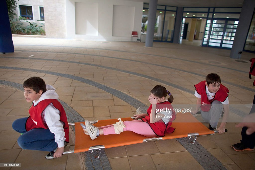 RA'ANANA, ISRAEL - FEBRUARY 14: Israeli schoolchildren act as the wounded during a Home Front command drill simulating a rocket hitting a school on February 14, 2013 in Ra'anana, Israel. Working with the schools and emergency services, local authorities want to increase readiness for possible future attacks.