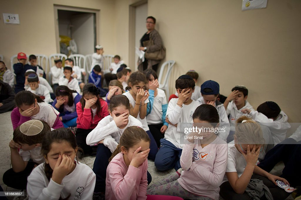 Israeli schoolchildren pray as they take cover in a bomb shelter during a Home Front command drill simulating a rocket hitting a school on February 14, 2013 in Ra'anana, Israel. Working with the schools and emergency services, local authorities want to increase readiness for possible future attacks.